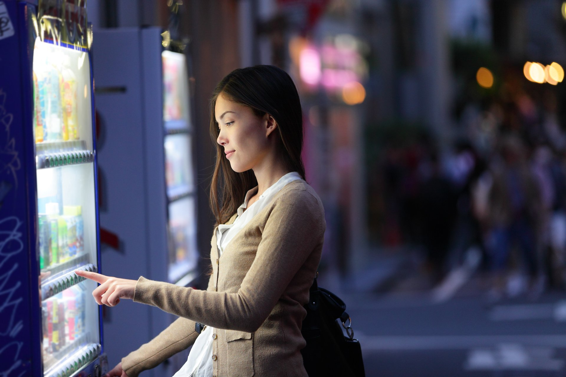 Young woman choosing a snack or drink at vending machine at night.